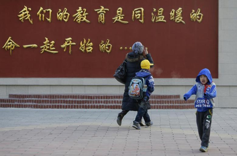 Liu Fei (L), 41-year-old warehouse worker, takes her son Xiaojie to school in Fangshan, district of Beijing, December 6, 2013. REUTERS/Jason Lee