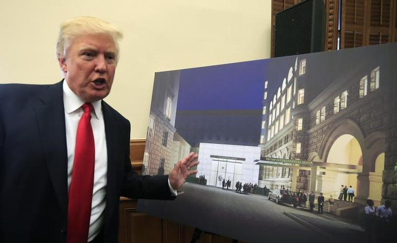 U.S. real-estate mogul Donald Trump gestures next to an architectural rendering of The Trump Organization's $200 million redevelopment of the iconic Old Post Office building into a luxury hotel, in Washington September 10, 2013. REUTERS/Kevin Lamarque