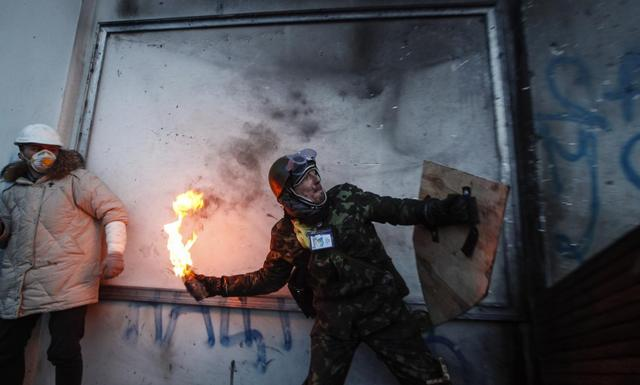 A pro-European integration protester throws a Molotov cocktail towards riot police during clashes in Kiev January 20, 2014. REUTERS/Vasily Fedosenko