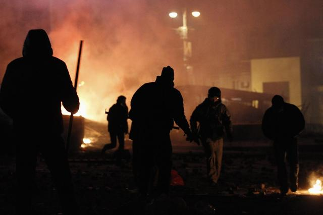 Pro-European protesters run past burning vehicles during clashes with Ukranian riot police in Kiev January 20, 2014. REUTERS/Gleb Garanich