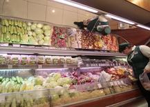 Женщина выбирает овощи в супермаркете в Москве 3 июня 2011 года. Крупный российский продуктовый ритейлер Окей увеличил торговую выручку без НДС за 2013 год на 18,7 процента до 137,7 миллиарда рублей - чуть ниже собственного прогноза, сообщила компания в среду. REUTERS/Alexander Natruskin