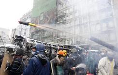 Сторонники евроинтеграци запускают пиротехнический снаряд в ходе столкновений с милицией в Киеве 22 января 2014 года. Бронированная машина выехала на улицу Грушевского в центре Киева, где милиция дубинками теснит протестующих на подступах к парламенту и правительству Украины. REUTERS/Vasily Fedosenko