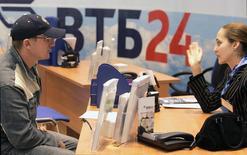 Сотрудник банка ВТБ разговаривает с клиентом в отделении в Москве 27 апреля 2007 года. Центральный банк РФ ждет роста корпоративного кредитования в 2014 году более чем на 10 процентов и замедления розничного до 25 процентов, сказал зампред ЦБ Михаил Сухов журналистам. REUTERS/Alexander Natruskin