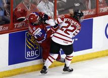 Canada's Hayley Wickenheiser hits Russia's Anna Shibanova during the second period of their semi-final game at the IIHF Ice Hockey Women's World Championship in Ottawa April 8, 2013. REUTERS/Chris Wattie