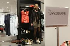 Женщина примеряет обувь в только что открывшемся магазине H&M в Москве 12 марта 2009 года. REUTERS/Denis Sinyakov