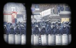 Бойцы украинской милиции на месте столкновений с протестующими в центре Киева 23 января 2014 года. Белый дом в четверг осудил насилие в Киеве, призвал все стороны к его прекращению и пригрозил Украине санкциями, если ситуация не улучшится. Комиссар ЕС по внешней политике Кэтрин Эштон заявила, что отправляется в Киев в попытке найти политическое решение кризиса. REUTERS/David Mdzinarishvili