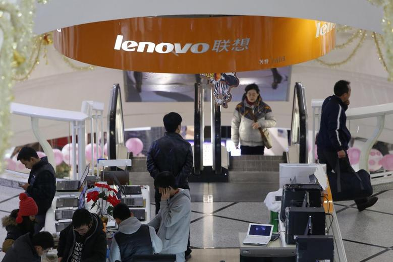 People stand under a sign showing the Lenovo company at a computer market in Shanghai January 21, 2014. REUTERS/Aly Song