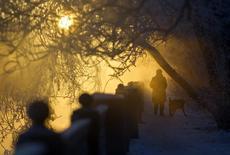 Женщина с собакой на берегу реки морозным днем в Москве 24 декабря 2012 года. Морозная температура не собирается покидать Москву - выходные обещают столице стужу с ночными температурами до минус 20. REUTERS/Maxim Shemetov