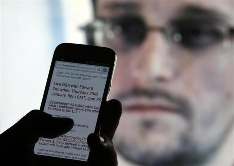 A man uses his cell phone to read updates about former U.S. spy agency contractor Edward Snowden answering users' questions on Twitter in this photo illustration, in Sarajevo, January 23, 2014. REUTERS/Dado Ruvic