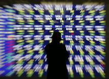 A man looks at at an electronic stock quotation board outside a brokerage in Tokyo January 14, 2014. REUTERS/Issei Kato