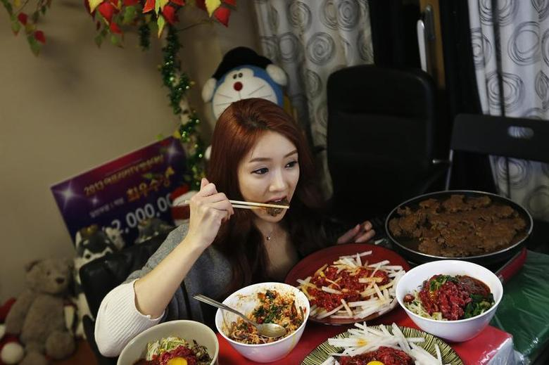 Park Seo-yeon, 34, eats in front of a video camera during her eating show in her apartment in Incheon, west of Seoul January 22, 2014. REUTERS/Kim Hong-Ji