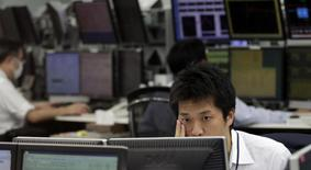 Сотрудники компании, торгующей валютой, за работой в Токио 8 апреля 2013 года. Азиатские фондовые рынки снизились до многомесячных уровней в понедельник, так как инвесторы продолжают бегство с развивающихся рынков. REUTERS/Toru Hanai