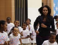 U.S. First Lady Michelle Obama jogs with children at a back-to-school event at Orr Elementary School in Washington September 6, 2013. REUTERS/Gary Cameron