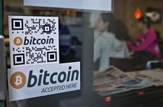 """Реклама банкомата, работающего с биткоинами, в кафе Waves Coffee House в Ванкувере 28 октября 2013 года. Центробанк РФ предупредил своих подопечных, что предоставление услуг юрлицам по обмену """"виртуальных валют"""" на рубли, иностранную валюту, товары и услуги будет рассматриваться регулятором, как потенциальная вовлеченность в сомнительные операции, сообщил ЦБ в понедельник. REUTERS/Andy Clark"""
