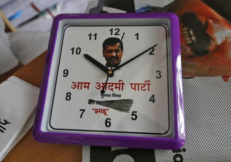 A wall clock carrying a portrait of Arvind Kejriwal, leader of the formed Aam Aadmi Party (AAP), and party symbol of a broom, lies on a table inside their party office in New Delhi October 1, 2013. REUTERS/Mansi Thapliyal/Files