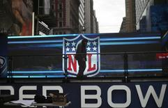 A worker walks on a stage in front of the NFL logo in New York's Times Square January 27, 2014. REUTERS/Mike Segar