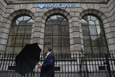 A man lifts his umbrella as he walks past a branch of Barclays bank in London July 30, 2013. REUTERS/Toby Melville