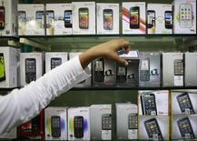 Um funcionário pega um celular da Micromax de uma prateleira em uma loja em Mumbai. As vendas mundiais de celulares inteligentes ultrapassaram 1 bilhão de unidades pela primeira vez em 2013, crescendo 38,4 por cento ante o ano anterior para 1,004 bilhão de unidades, disse a empresa de pesquisa IDC. 04/12/2013 REUTERS/Danish Siddiqui