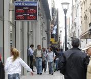 Unas personas caminan junto a una casa de cambios en Buenos Aires, ene 24 2014. Argentina está siendo víctima de un ataque de especuladores para quebrarla y quedarse con sus recursos energéticos y naturales a precios de remate, aseguró el martes el Gobierno del país en su búsqueda de una explicación de la fuerte devaluación que registró la moneda local la semana pasada. REUTERS/Enrique Marcarian