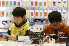 Unos jóvenes prueban unos teléfonos Galaxy de Samsung en la casa matriz de la firma en Seúl, ene 23 2014. Samsung Electronics Co Ltd vendió un récord de 86 millones de teléfonos inteligentes en el cuarto trimestre y amplió su ventaja respecto de Apple Inc, incluso aunque la firma estadounidense registró un nuevo máximo de ventas para su iPhone, según datos de la consultora Strategy Analytics. REUTERS/Kim Hong-Ji