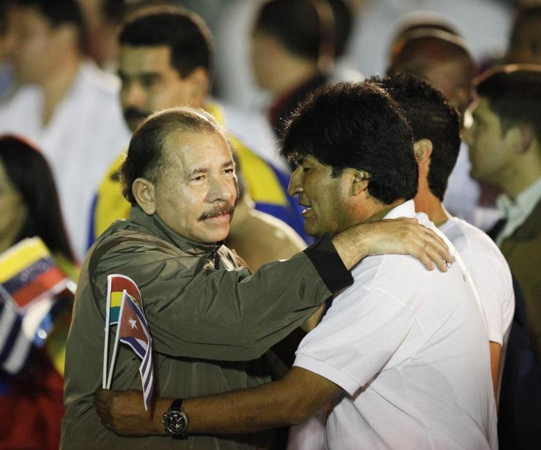 Nicaragua's President Daniel Ortega (L) hugs his Bolivian counterpart Evo Morales before the march of the torches in celebration of the 161th birth anniversary of Cuba's independence hero Jose Marti in Havana January 27, 2014. REUTERS/Claudia Daut