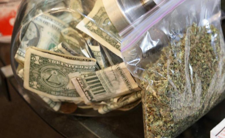 A bag of marijuana being prepared for sale sits next to a money jar at BotanaCare in Northglenn, Colorado December 31, 2013. REUTERS/Rick Wilking