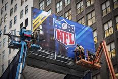 Workers hang signage on a booth on Broadway as preparations continue for Super Bowl XLVIII in New York January 28, 2014. REUTERS/Lucas Jackson