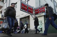 Люди проходят мимо вывески пункта обмена валюты в Москве 27 января 2014 года. Рубль ушел в минус днем среды, достиг границы валютного коридора и упал ниже 35 рублей за доллар впервые с марта 2009 года после утреннего роста в ответ на неожиданное решение турецкого ЦБ резко ужесточить денежно-кредитную политику. Радость рынков сменилась сомнениями по поводу долгосрочного эффекта от столь резкого повышения ставок и вернула внимание инвесторов к доминировавшей в последние дни теме сокращения денежной эмиссии в США. REUTERS/Maxim Shemetov