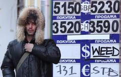 Мужчина проходит мимо вывески пункта обмена валюты в Москве 29 января 2014 года. Рубль рухнул к пятилетним минимумам вслед за валютами развивающихся рынков, поскольку инвесторов не убедили меры поддержки национальных валют Центробанка Турции, а вечером и ЦБ ЮАР, повысивших ключевые ставки. REUTERS/Sergei Karpukhin