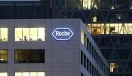 Логотип Roche на заводе компании в деревне Роткройц 6 ноября 2013 года. Сильный швейцарский франк оставил след на годовой прибыли Roche, пообещавшей увеличить дивиденды. REUTERS/Arnd Wiegmann