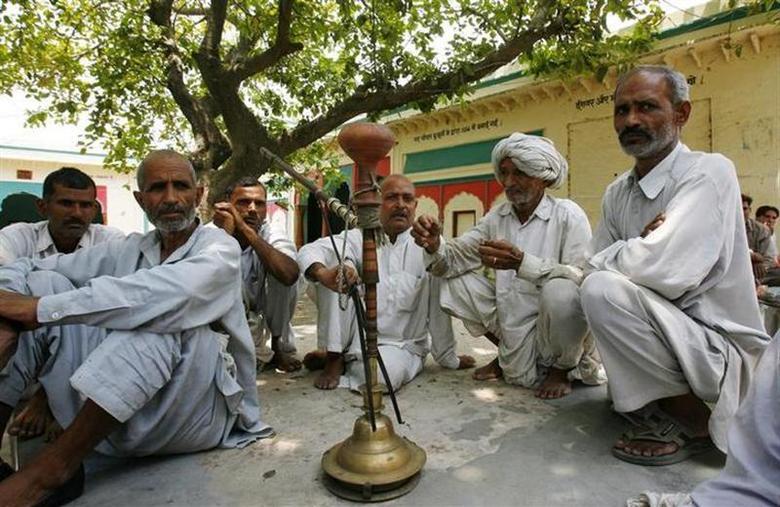 Villagers sit after attending a panchayat, or village council meeting, at Balla village in Haryana May 13, 2008. REUTERS/Vijay Mathur/Files