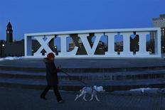 A woman walks with her dog next to roman numerals for NFL Super Bowl XLVIII football game in Hoboken, New Jersey, January 30, 2014. REUTERS/Eduardo Munoz