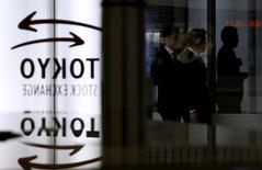 Люди проходят мимо логотипа Токийской фондовой биржи в Токио 30 января 2014 года. Японский фондовый индекс Nikkei в пятницу снизился до минимума 2,5 месяцев из-за укрепления иены. REUTERS/Toru Hanai