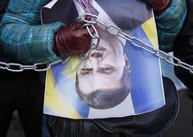 Участник протестов держит перевернутое изображение президента Украины Виктора Януковича в ходе акции протеста в Киеве 26 декабря 2013 года. Янукович подписал решение парламента отменить принятые 16 января законы, ужесточавшие наказание за участие в антиправительственных протестах и вызвавшие эскалацию политического кризиса. REUTERS/Gleb Garanich