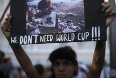 """Manifestante ergue cartaz durante um protesto contra a Copa do Mundo de 2014, em Copacabana, no Rio de Janeiro. Preocupado com o movimento """"não vai ter Copa"""" e com as críticas sobre a organização e os gastos para realização da Copa do Mundo, o governo prepara uma ofensiva com foco publicitário para reagir e transformar o evento em dividendo político para a presidente Dilma Rousseff, disse uma fonte do Executivo nesta sexta-feira. 25/01/2014. REUTERS/Ricardo Moraes"""