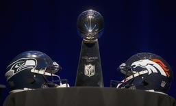 O troféu Vince Lombardi e os capacetes dos Seattle Seahawks e dos Denver Broncos em uma mesa antes da coletiva de imprensa com os técnicos antes do Super Bowl, em Nova York. Mais de 100 milhões de pessoas estarão com os olhos grudados em seus televisores no domingo, quando os dois times se enfrentarem no mais importante evento esportivo dos Estados Unidos, o Super Bowl. 31/01/2014 REUTERS/Carlo Allegri