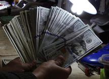 Un empleado revisa unos dólares en una casa de cambios en Manila, ene 15 2014. El euro caía el viernes frente al dólar y el yen, ya que una inesperada desaceleración en la inflación de la zona euro reavivó las preocupaciones respecto a que el Banco Central Europeo (BCE) podría tener que actuar para combatir la deflación. REUTERS/Romeo Ranoco