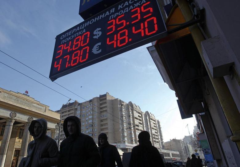 People walk past a currency exchange showing rouble exchange rates in Moscow January 30, 2014. REUTERS/Maxim Shemetov