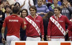 Switzerland's Roger Federer (C) and Michael Lammer (R) congratulate Stanislas Wawrinka (L) after winning his Davis Cup world group first round tennis match against Serbia's Dusan Lajovic in Novi Sad January 31, 2014. REUTERS/Novak Djurovic