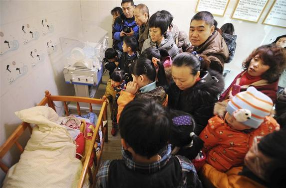Residents visit an abandoned baby (L) lying in a crib at a baby hatch in Guiyang, Guizhou province January 12, 2014. REUTERS-Stringer