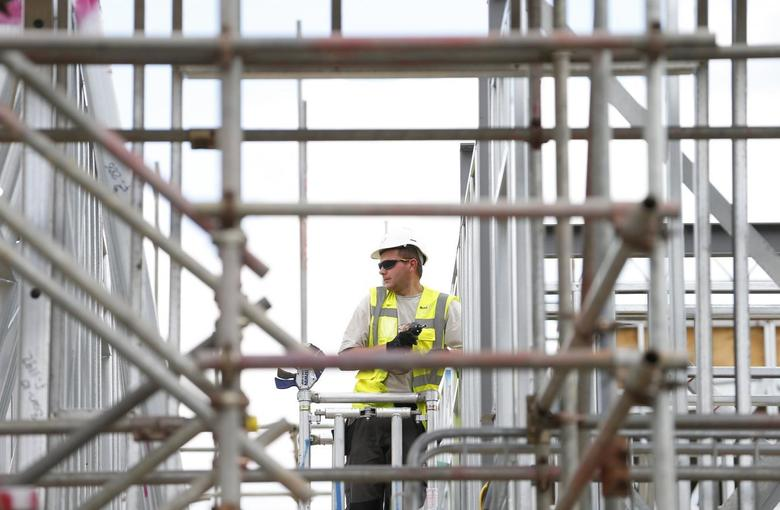 A construction worker assembles metal frames at a housing development project in south London August 6, 2013. REUTERS/Andrew Winning