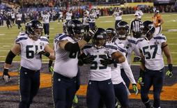 Seattle Seahawks' Malcolm Smith (2nd R) celebrates scoring a touchdown on an interception against the Denver Broncos with teammates J.R. Sweezy (L), Breno Giacomini and Mike Morgan (R) in the second quarter of the NFL Super Bowl XLVIII football game in East Rutherford, New Jersey, February 2, 2014. REUTERS/Brendan McDermid