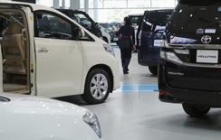 A woman walks among Toyota Motor's cars at the company's showroom in Tokyo November 6, 2013. REUTERS/Toru Hanai