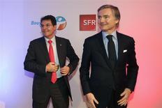 Jean-Yves Charlier (à droite), PDG de SFR, et Olivier Roussat, PDG de Bouygues Telecom, à l'issue d'une conférence de presse à Paris lundi consacrée à l'accord de mutualisation que les deux entreprises concurrentes viennent de conclure. Jean-Yves Charlier a précisé que SFR espérait entrer en Bourse début juillet/Photo prise le 3février 2014/ /REUTERS/Charles Platiau