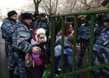 Полицейские эвакуируют детей из школы на окраине Москвы, где старшеклассник растрелял двух человек 3 февраля 2014 года. Вооруженный ученик старших классов школы на окраине Москвы захватил класс утром в понедельник, убил учителя и полицейского, после чего был пойман, а заложники - освобождены, сообщила полиция. REUTERS/Maxim Shemetov