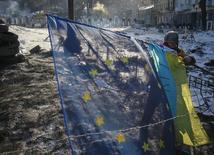 Антиправительственный демонстрант размахивает флагами Украины и ЕС на баррикаде в Киеве 2 февраля 2014 года. Украинские евробонды, номинированные в долларах, взлетели в цене в понедельник на спекуляциях о том, что Киев может получить финансовую поддержку западных держав. REUTERS/Gleb Garanich
