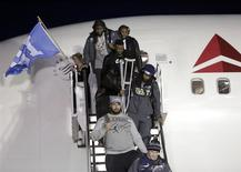 Seattle Seahawks' Richard Sherman (R) carries his crutches as he exits the team's chartered flight home after winning NFL Super Bowl XLVIII at Seatac Airport in Seattle, Washington February 3, 2014. REUTERS/Jason Redmond