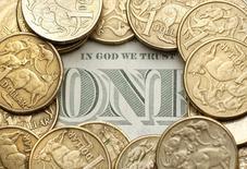Монеты достоинством 1 австралийский доллар лежат на купюре номиналом 1 доллар США в Сиднее 27 июля 2011 года. Австралийский доллар взлетел на торгах вторника после того, как Центробанк страны удивил некоторых трейдеров нейтральной риторикой, развеяв надежды на дальнейшее снижение ставок. REUTERS/Tim Wimborne