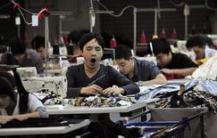 Рабочий зевает в цеху текстильной фабрики в городе Хумэн в провинции Гуандун 24 ноября 2013 года. Медленный рост китайского и американского производственных секторов заставил волноваться о мировой экономике, несмотря на то, что для европейских производителей 2014 год начался удачно. REUTERS/Stringer