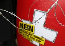 A poster against the 'mass immigration initiative' of the Swiss Socalist Party SPS is seen through barbed wire fence on the Federal Square before a campaign in Bern January 29, 2014. REUTERS/Ruben Sprich